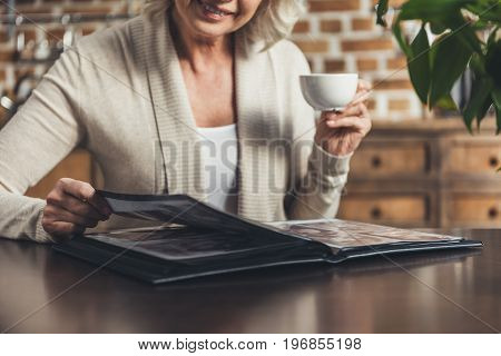 Portrait Of Senior Woman Sitting At Kitchen Table And Looking At Photo Album