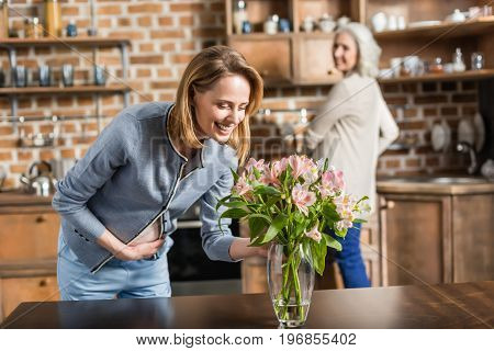 Portrait Of Young Pregnant Woman And Her Senior Mother With Bouquet Of Flowers On Kitchen