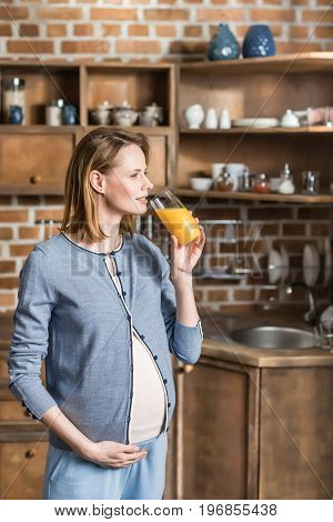 Portrait Of Young Pregnant Woman With Glass Of Juice On Kitchen