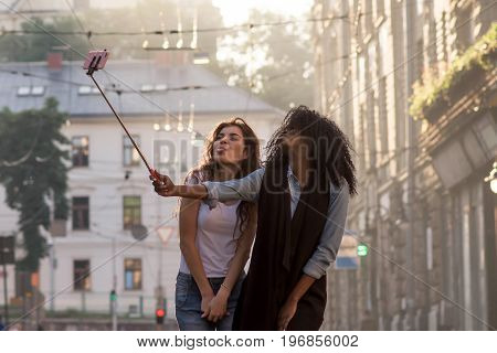 Two friends posing for camera making selfie. Happy young women. One woman is black.