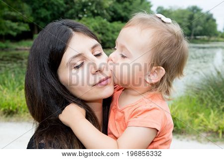 Little Girl Daughter Kiss Cheerful Mother In Park Near Lake