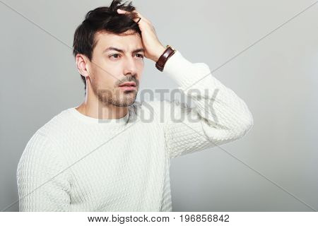 handsome young man hold his head in hand forgotten something