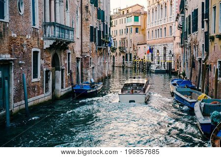 VENICE, ITALY - JULY 01, 2017: Private boat on a canal in Venice. Venice is an popular tourist destination for its uniqueness and celebrated art and architecture.