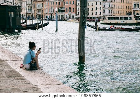 VENICE, ITALY - JULY 02, 2017: Young woman relaxes on the bank of Grand Canal browsing mobile phone. The canal is the major water-traffic corridor in the city.
