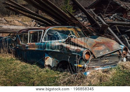 Old rusty classic car from the fifties left to rot in a field on a desertet farm in Sweden
