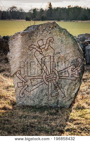 Old rune stone from Sweden with a signet or seal in the shape of a cross