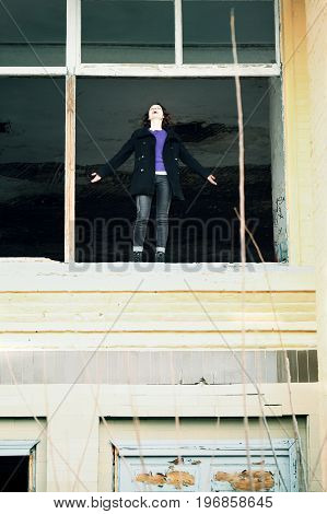 young woman standing in the window of an abandoned house