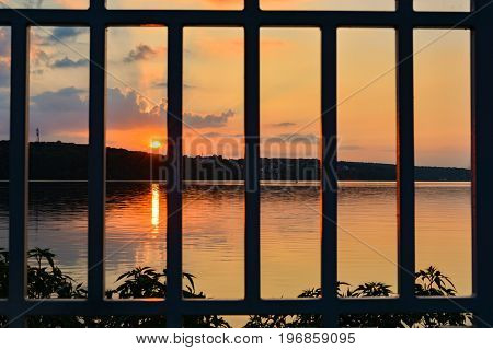 Sunset over a lake with clouds and sky red, blue, orange and blue. Lattice. Prison.