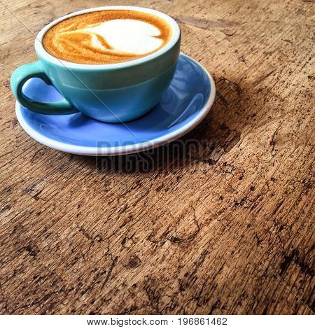 Hot art Latte Coffee in a cup in coffee shop on wooden table with vintage style effect close up with copy space