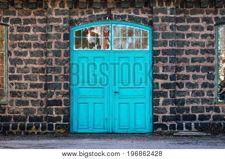 Turquoise entrance door to a very old steel mill made of cinder stones