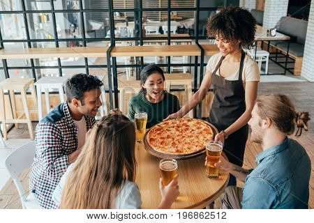 African American Woman Waitress Bringing Pizza For Clients In Cafe