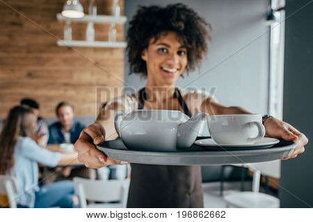 Smiling african american waitress holding tray with tea and customers sitting behind her in cafe