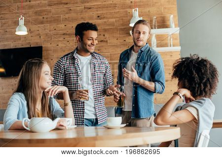 Two Men Are Wary Of Young Women Sitting In Cafe