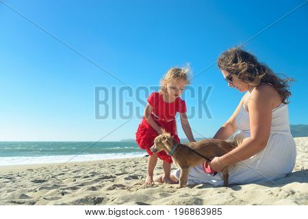 Mother and daughter on the beach, sitting on the sand, girl in red dress playing with the dog. Candid shot, real people.