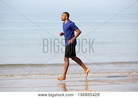 Full Length Young Black Man Jogging Along The Beach