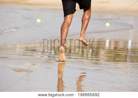 Young Man Running Barefoot On Beach