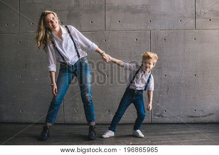 Mother and son pulling hands each other on the wall background
