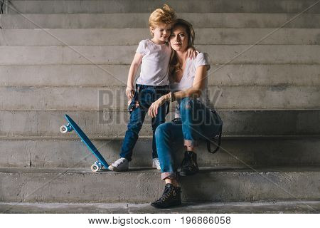 Mother with son on the skateboard standing on a stairs