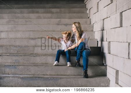 Mother with son sitting on a stairs and looking somewhere