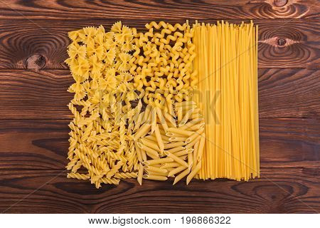 Beautiful variety of pasta on a dark wooden background. Different kinds of perfectly organized macaroni on a brown table. Delicious farfalle, fettuccine, noodles, fusilli and penne rigate.