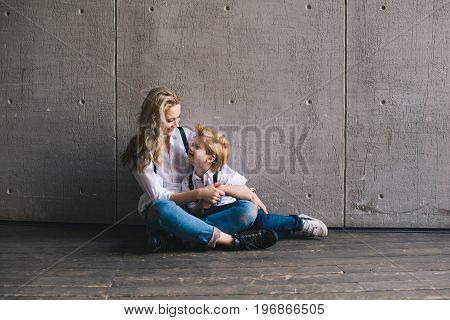 Mother hugging with son and sitting at a wall