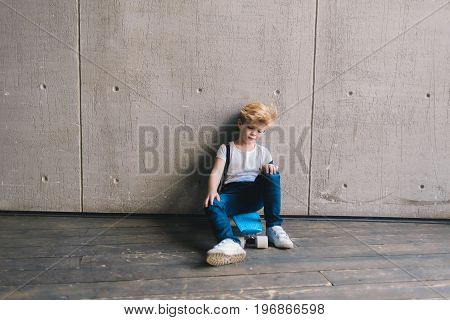 Little boy sitting on a skateboard at a wall
