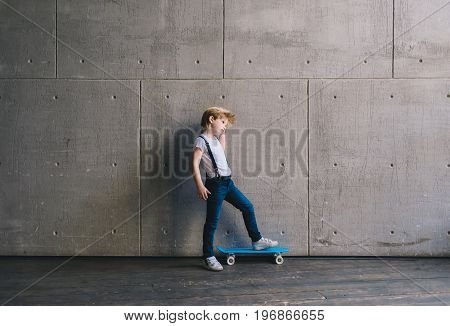 Little boy standing with a skateboard at a wall