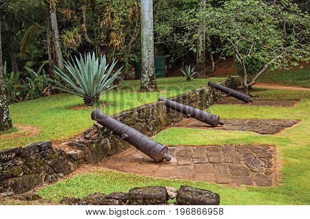 View of fortress cannons amid tropical landscape on cloudy day near Paraty, an amazing and historic town totally preserved in the coast of the Rio de Janeiro State, southwestern Brazil