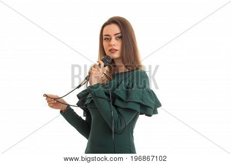 Cute brunette lady in green dress with microphone isolated on white background
