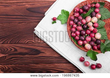Tasty, juicy, healthy, ripe multicolored gooseberries with green leaves in a basket on a dark brown wooden table. Juicy, raw, fresh, tasty, healthy, nutritious concept.
