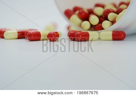 Antibiotic capsule pills with bottle on white background