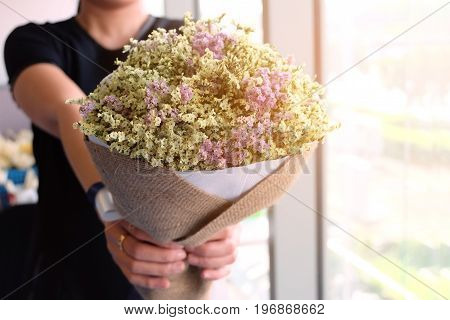 Girl hands giving a bouquet of flowers.