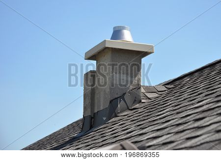 Chimney Repair and Waterproofing asphalt shingles. New modular pumice chimney installation on the house roof. Chimney Linings. Pumice chimney liners.