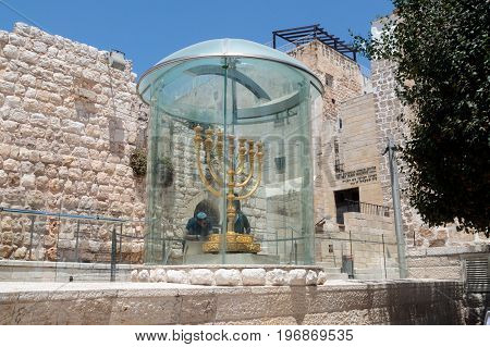 Jerusalem Israel July 14 2017 : Tourists view Menorah - the golden seven-barrel lamp - the national and religious Jewish emblem near the Dung Gates in the Old City of Jerusalem Israel