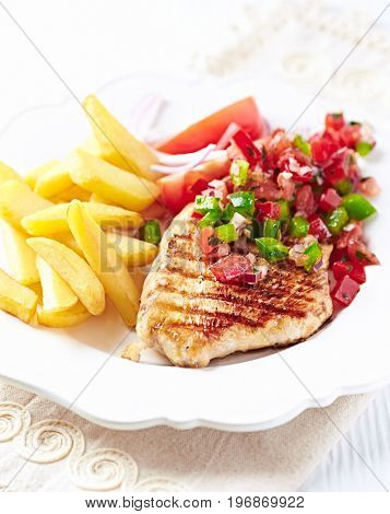 Grilled turkey breast with salsa and french fries
