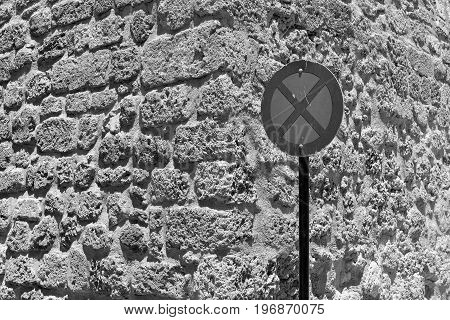 one street sign the stop is forbidden by a closeup against the background of an old stone wall of monochrome tone