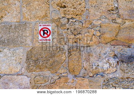 one street sign the parking of motor transport is forbidden on an old stone wall