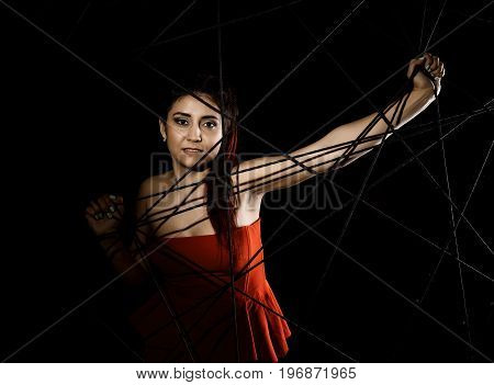 beautiful young woman in red dress entangled in a rope cobweb on a black background.