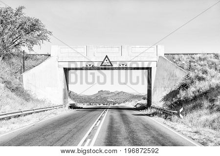 A monochrome view of a railway bridge over the B1-road frames a mountain scene south of Windhoek the capital city of Namibia