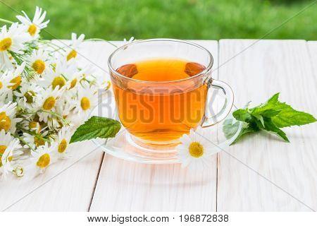 Chamomile tea on a light wooden table.