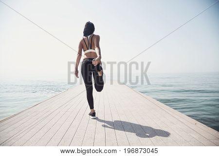 Young beautiful sportive girl preparing to run over seaside.