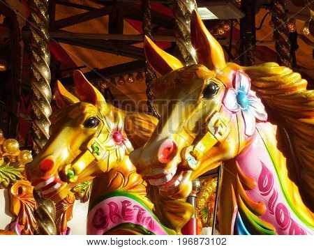 brightly coloured carousel horses on a vintage fairground ride