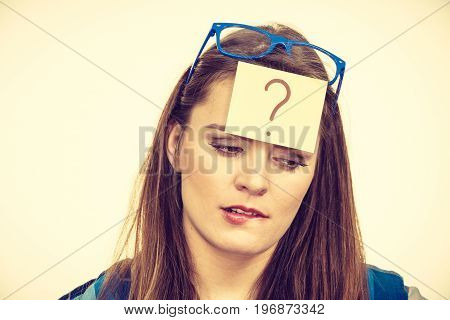 Thinking woman with big nerdy eyeglasses and question mark on forehead on beige bright. Creating new idea studying and education concept.