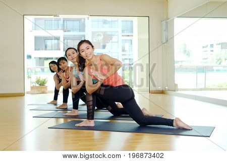 Group of asian women training yoga indoor class in namaste posture with joyful relax and meditate emotion wellness well being and healthy lifestyle concept