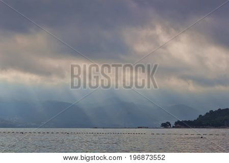 Clouds over the Adriatic Sea. In the gaps the sun's rays. The Budva Riviera