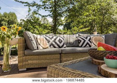 Closer shot of a garden sofa with the vase of sunflowers standing close
