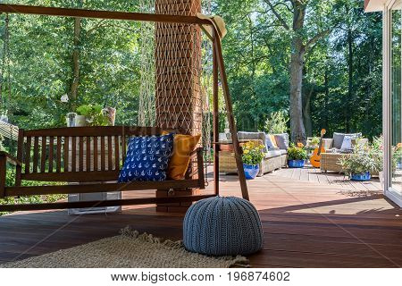 Wooden garden swing located in a shaded corner of a house terrace