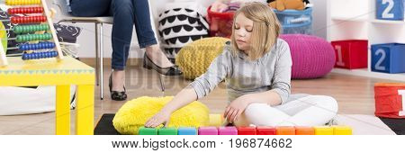 Young girl on psychotherapy playing with colorful blocks