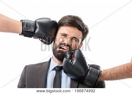 Portrait Of Businessman Getting Punched By Boxers Isolated On White