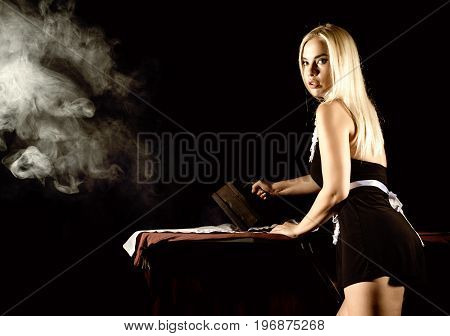 back view of sexy blonde woman in housekeeper suit, ironing white shirt with old iron. retro style. housewife concept
